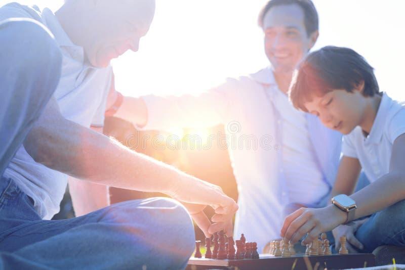 Дружелюбная семья играя шахмат совместно стоковое фото