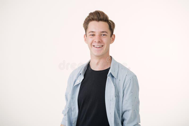Дружелюбный выглядя красивый молодой человек нося положение голубой рубашки усмехаясь над белой предпосылкой стоковые фото