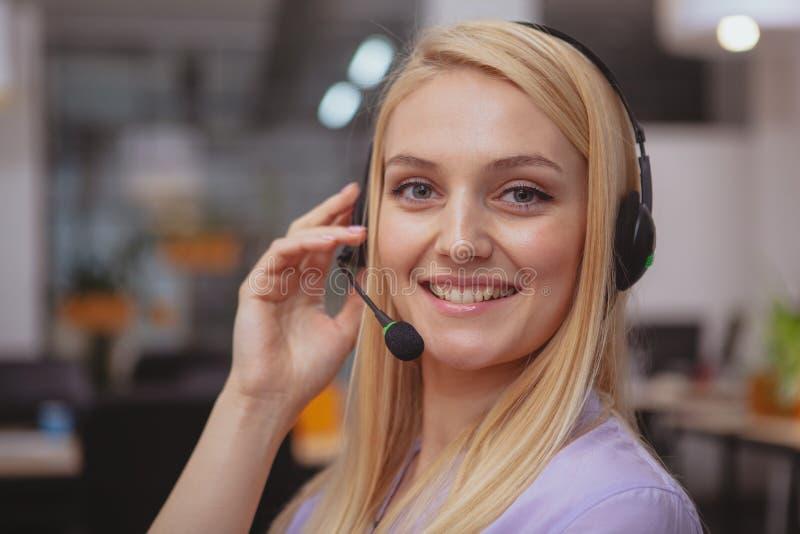 Дружелюбный оператор работы с клиентом с деятельностью шлемофона в центре телефонного обслуживания стоковые фотографии rf