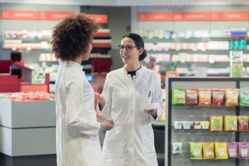 2 дружелюбных коллеги говоря пока работающ совместно как аптекари стоковое изображение