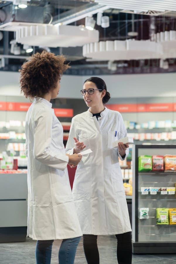 2 дружелюбных коллеги говоря пока работающ совместно как аптекари стоковые фото