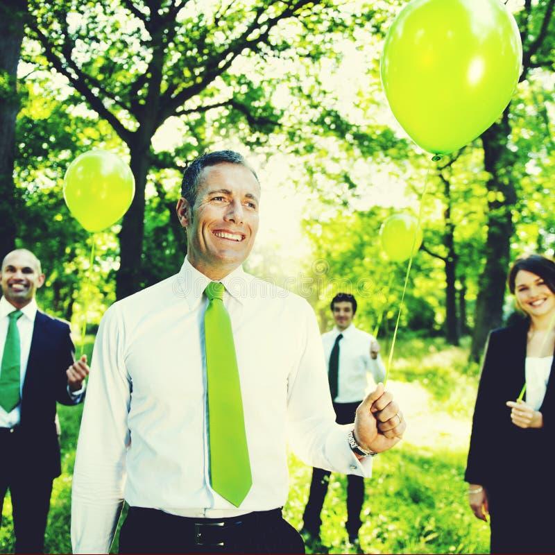 Дружественные к Эко бизнесмены держа зеленую концепцию воздушных шаров стоковые изображения