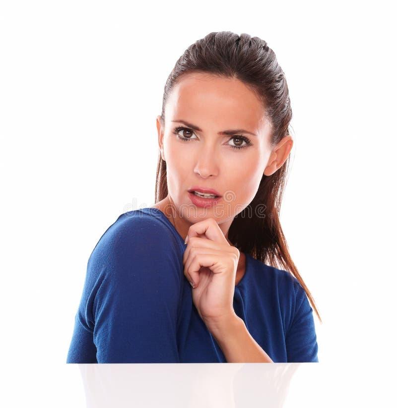 Дружелюбная дама в голубой блузке смотря интересуемый стоковая фотография