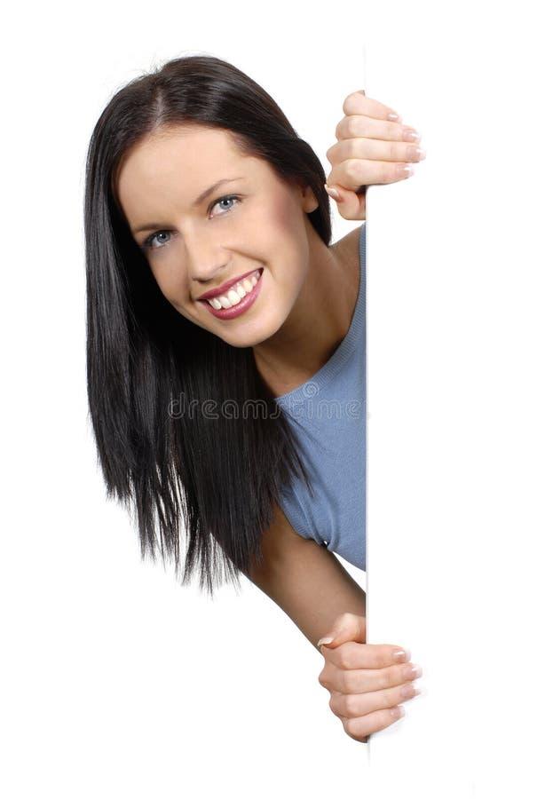 Дружелюбная девушка peeking вокруг белой доски стоковое изображение rf