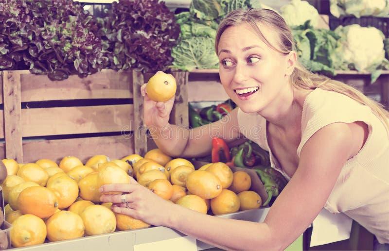 Дружелюбная женщина держа лимоны в руках в магазине плодоовощ стоковая фотография rf