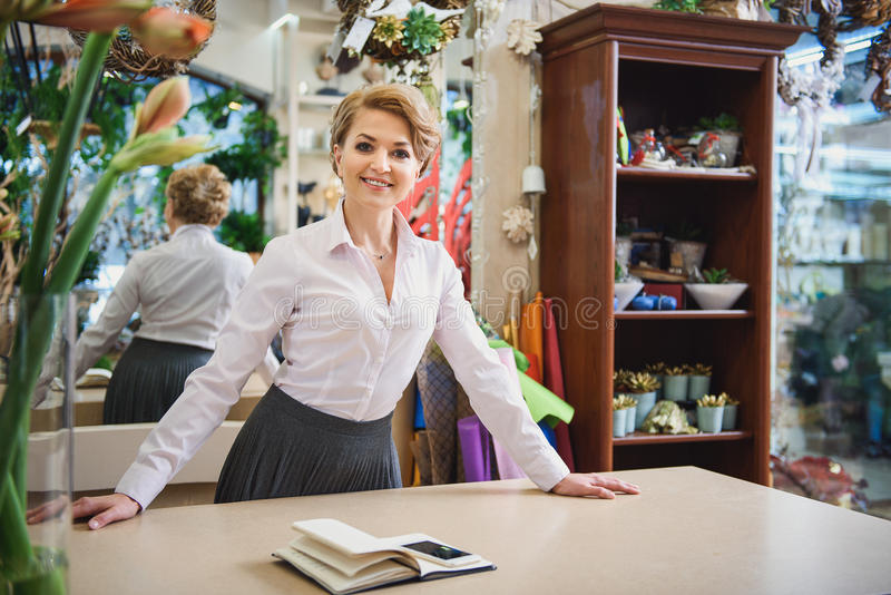 Дружелюбная женщина работая в цветочном магазине стоковые фотографии rf
