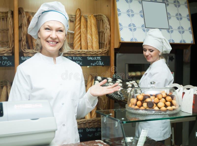 Дружелюбные женские хлебопеки с печеньем усмехаясь в хлебопекарне стоковое изображение rf