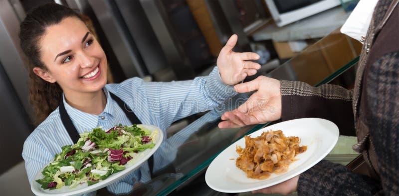 Дружелюбный клиент и усмехаться сервировки женского работника стоковые фото