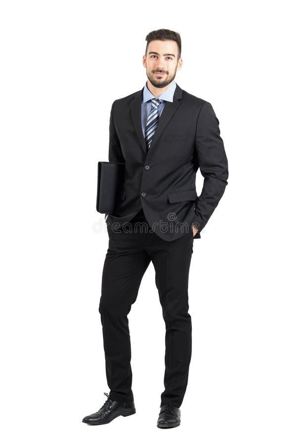 Дружелюбный молодой уверенно бизнесмен держа папку документов усмехаясь на камере стоковые фото