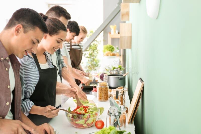 Друзья варя совместно в кухне стоковые изображения rf