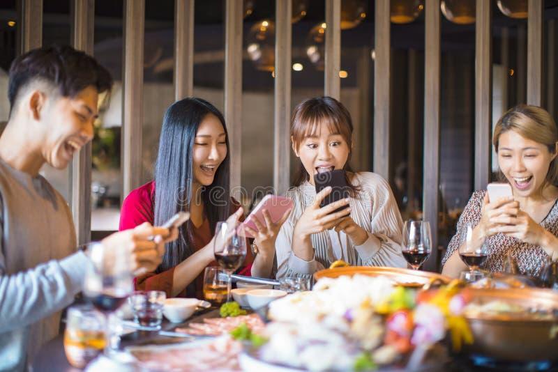 Друзья весело проводят время в ресторане и смотрят на смартфон стоковое фото rf
