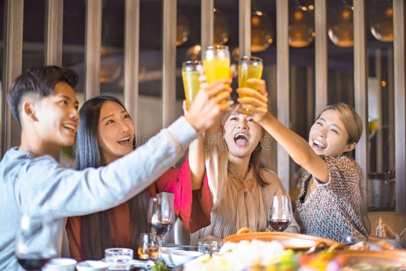 Друзья веселятся в ресторане с горячим кастрюлем стоковые изображения