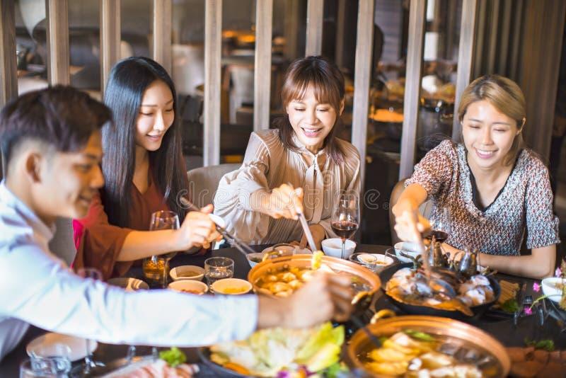 Друзья веселятся в ресторане с горячим кастрюлем стоковое фото rf