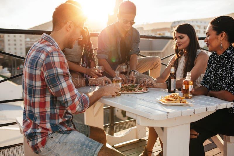 Друзья вися вне на крыше стоковое изображение