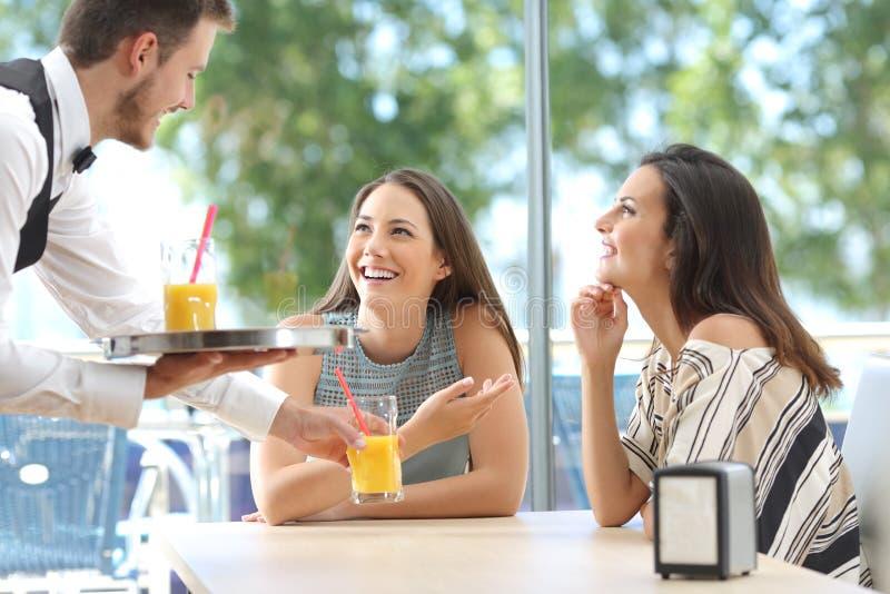 Друзья встречая в баре с сервировкой кельнера стоковое изображение rf