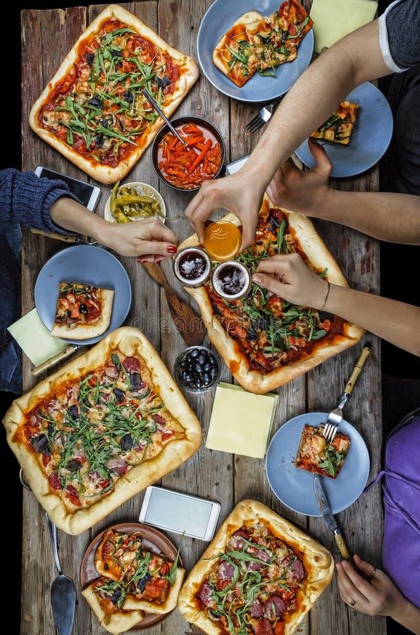 Друзья встречи, обедающий, дуя стекла, пиво, праздничные toas стоковые фотографии rf