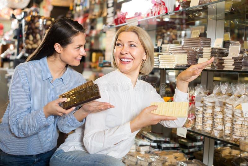 Друзья выбирая шоколады стоковая фотография
