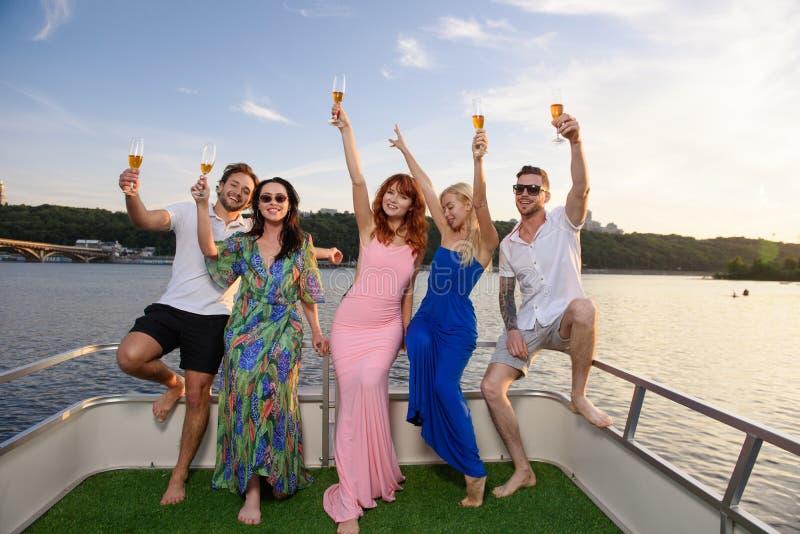 Друзья выпивают шампанское на яхте, во время захода солнца стоковые изображения rf