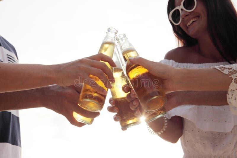 Друзья выпивая пиво на пляже стоковое изображение rf