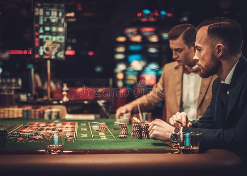 Друзья высшего класса играя в азартные игры в казино стоковая фотография