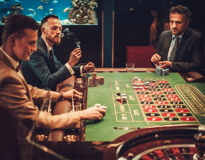 Друзья высшего класса играя в азартные игры в казино стоковая фотография rf