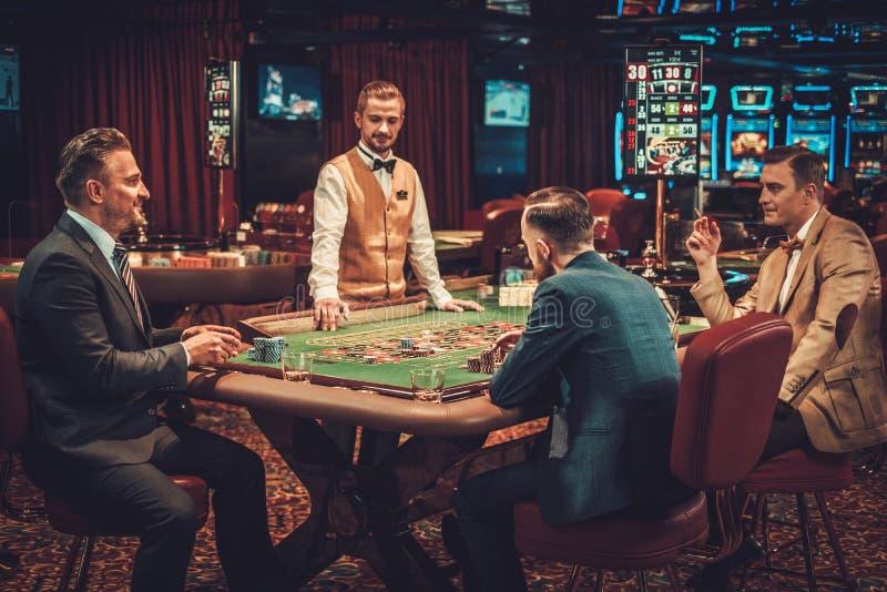 Друзья высшего класса играя в азартные игры в казино стоковые фото