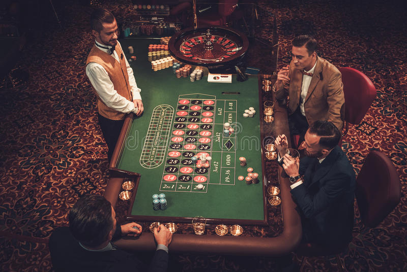 Друзья высшего класса играя в азартные игры в казино стоковое фото