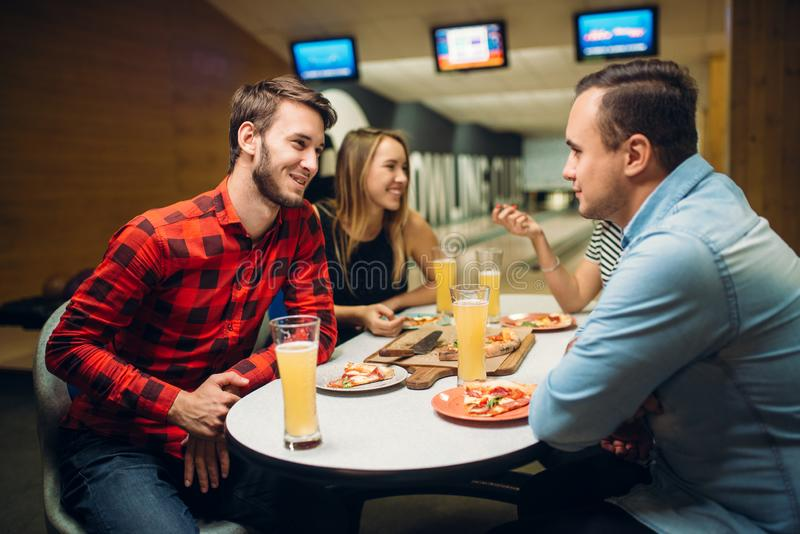 Друзья в клубе боулинга, доске игры на предпосылке стоковые фото