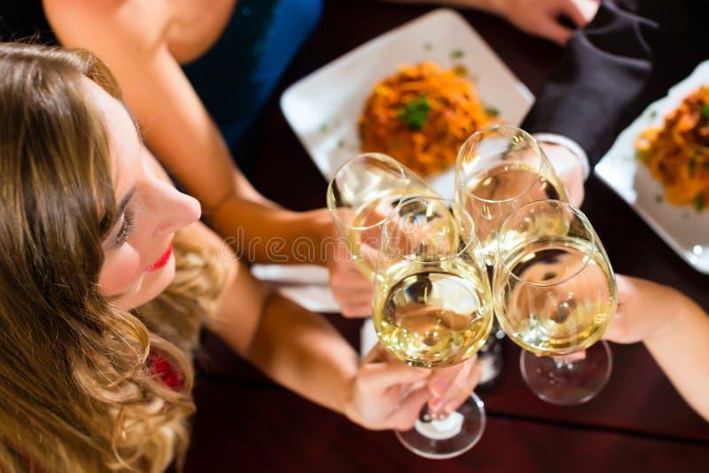 Друзья в стеклах очень хороших clink ресторана стоковые фотографии rf