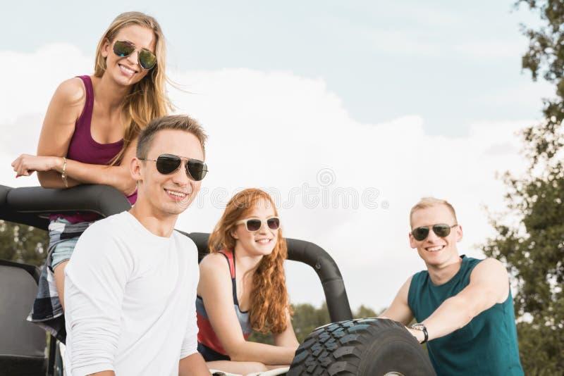 Друзья в с автомобиле дороги стоковая фотография