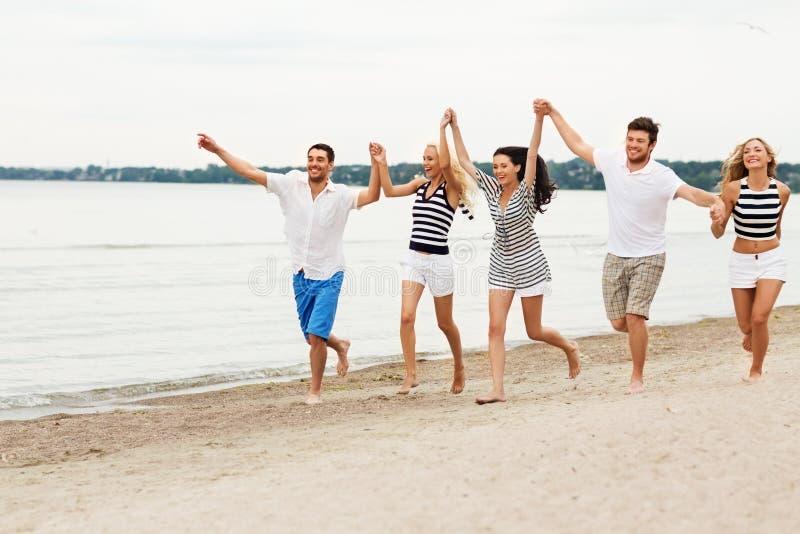 Друзья в striped одеждах бежать вдоль пляжа стоковые изображения rf