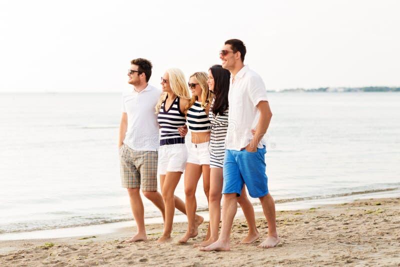 Друзья в striped одеждах идя вдоль пляжа стоковые изображения