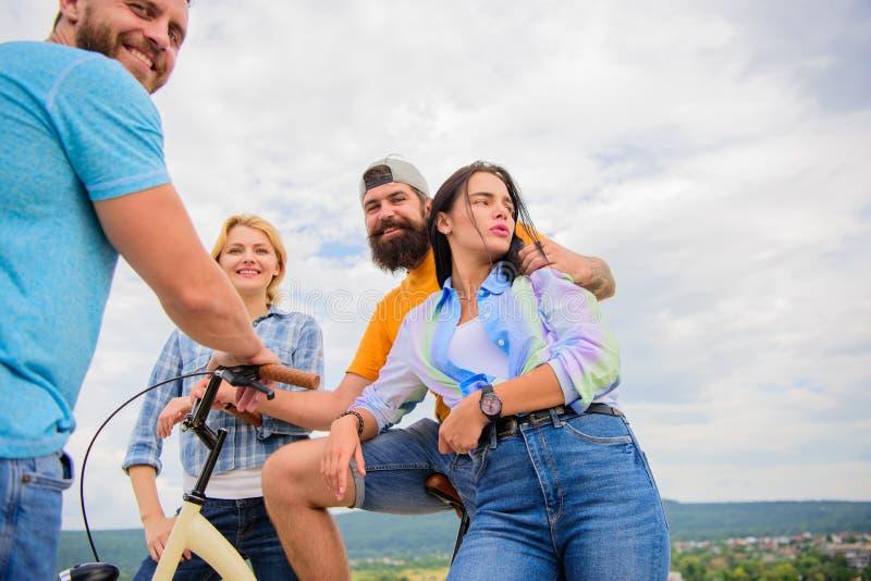Друзья группы висят вне с велосипедом Молодые люди компании стильное тратит предпосылку неба отдыха outdoors Встреча пар стоковые фото