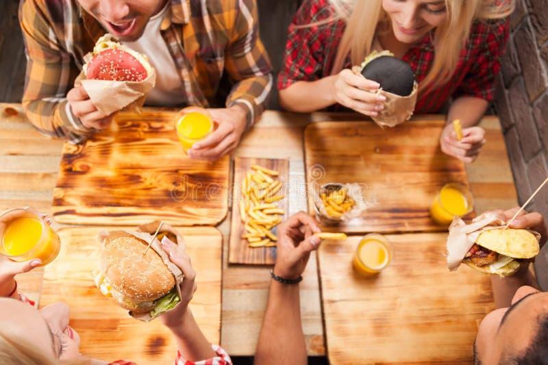 Друзья группы людей есть картошку бургеров фаст-фуда выпивая апельсиновый сок стоковое изображение
