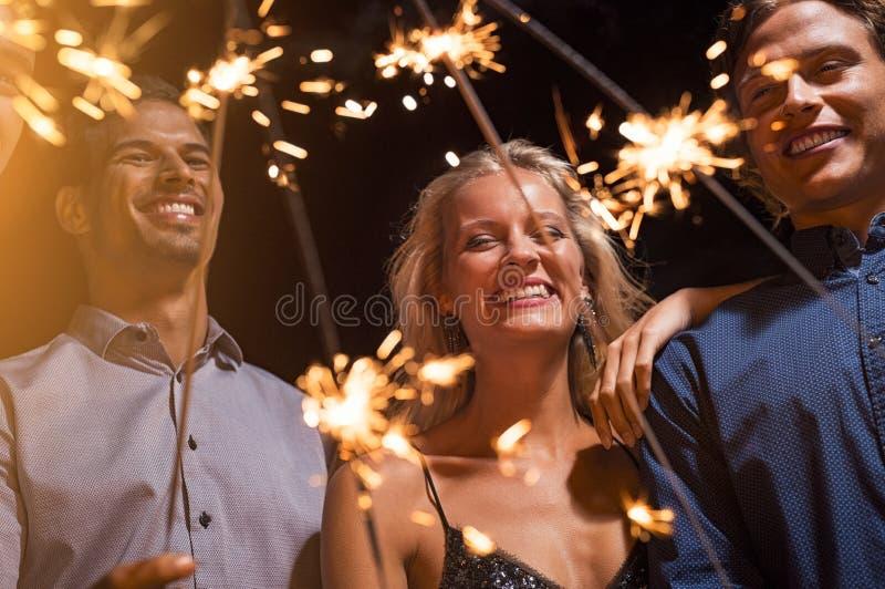 Друзья держа накаляя бенгальские огни на партии стоковое фото