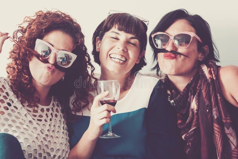 Друзья дома идя сумасшедший имеющ потеху - людей женщин в приятельстве совместно стоковая фотография