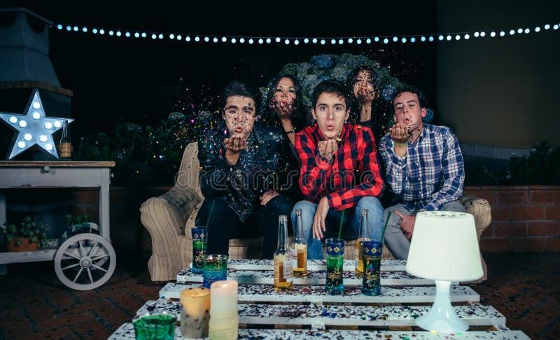 Друзья дуя confetti к камере в партии стоковое фото rf