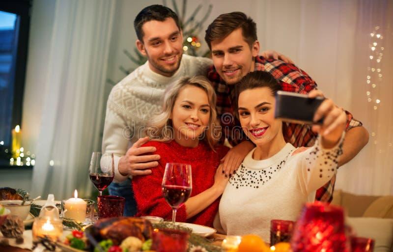 Друзья едят селфи на рождественском ужине стоковое фото rf