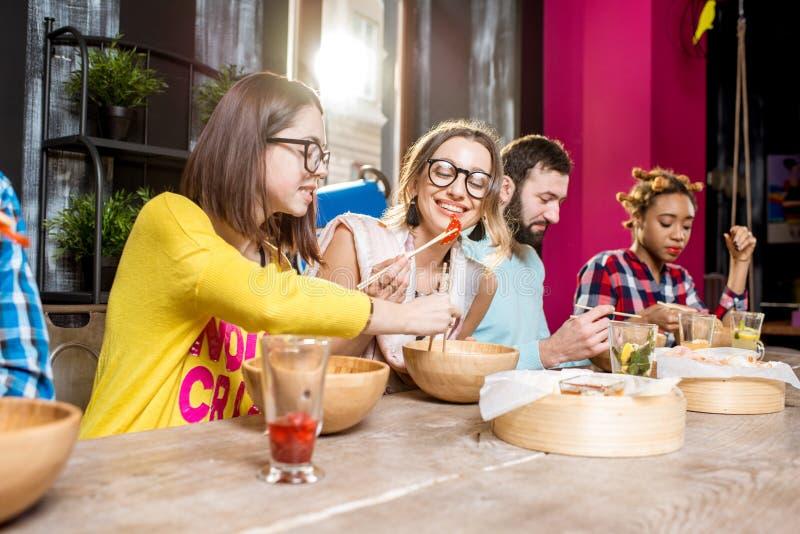 Друзья есть азиатские еды на ресторане стоковая фотография rf
