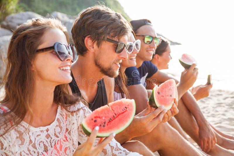 Друзья есть арбуз на пляже стоковое изображение
