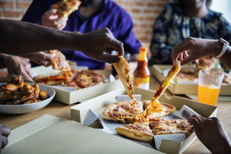 Друзья есть пиццу совместно дома стоковая фотография