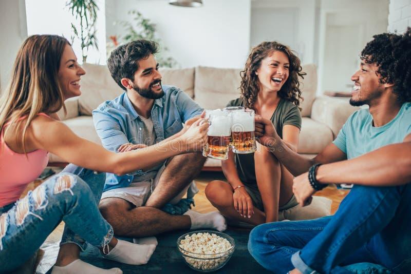 Друзья есть попкорн и выпивая кружку пива дома, имеющ потеху стоковое изображение rf