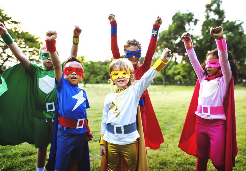 Друзья детей супергероев играя концепцию единения стоковая фотография rf