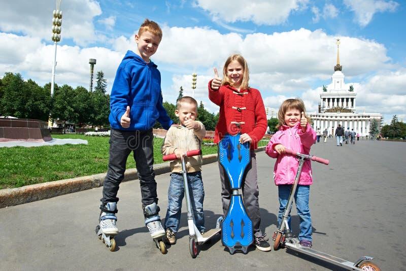 Друзья ехать скейтборд и самокат стоковые фотографии rf