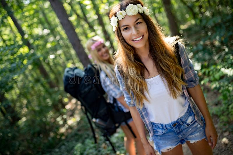 Друзья женщин Hiker с рюкзаком идя на путь в лесе лета стоковые фото