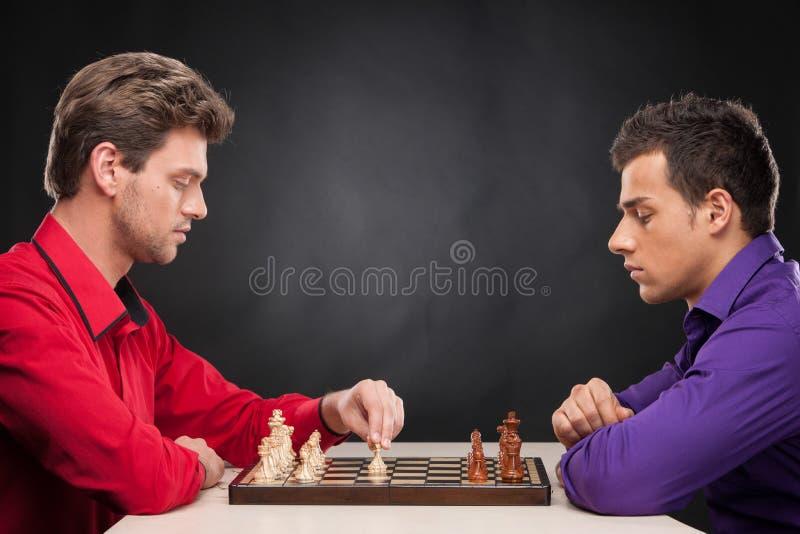 Друзья играя шахмат на черной предпосылке стоковые изображения