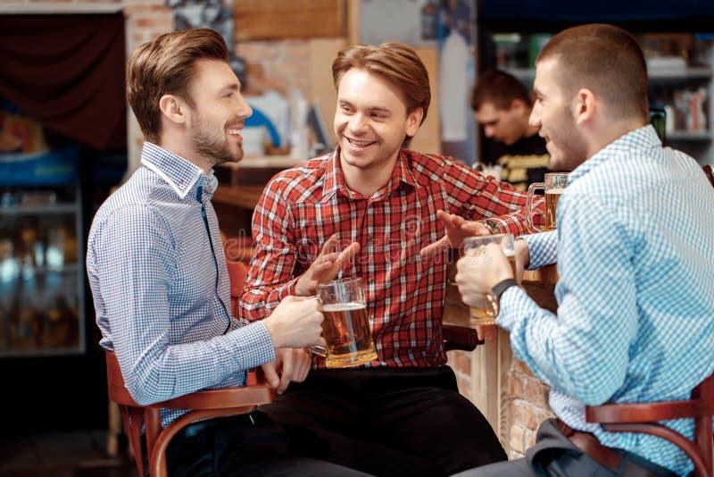 Друзья имеют пиво на пабе стоковые изображения