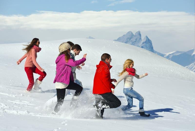 Друзья имеют потеху на зиме на свежем снеге стоковое фото rf