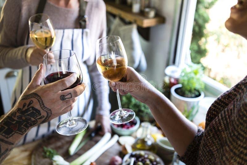 Друзья имея белое вино пока варящ в кухне стоковые фото