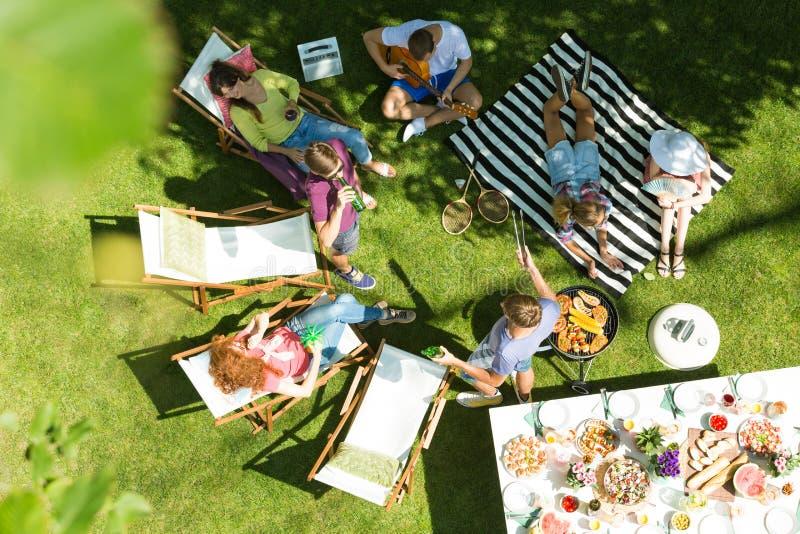 Друзья имея гриль в саде стоковая фотография